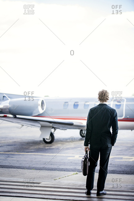 Businessman standing looking at personal plane