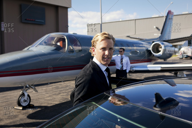 Business entering a limousine from his private jet
