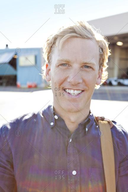 Portrait of man on tarmac near hangar