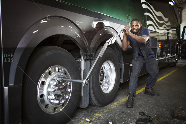 Bus mechanic using wrench to unscrew tire bolts