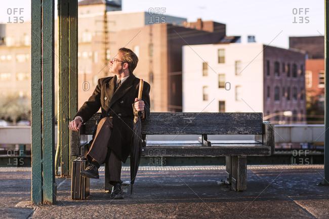 Man sitting on outdoor subway platform staring