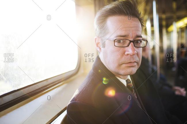 Man sitting on subway train looking at camera