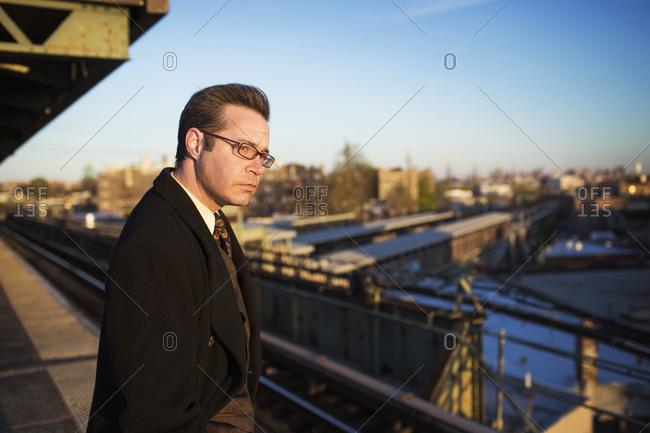 Man on rail platform staring off