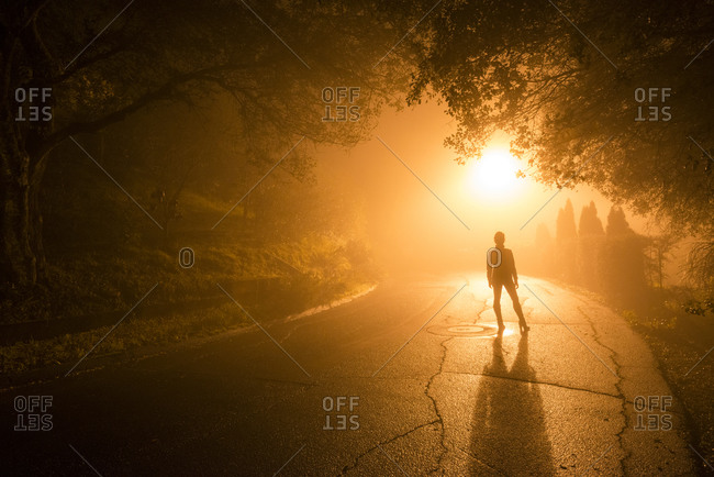 A woman standing on a foggy street at dawn in Healdsburg, California
