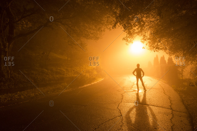 A woman stands on a foggy street at dusk in Healdsburg, California