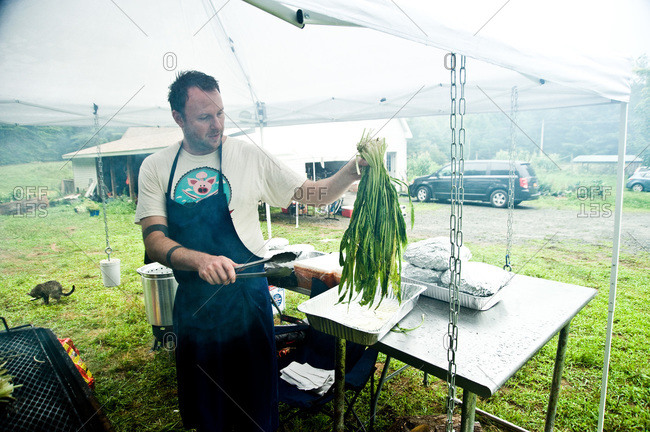 Narrowsburg, NY, USA - August 10, 2012: Man at barbecue holding up greens at the Pig Mountain festival
