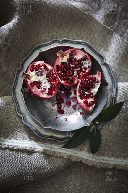 Pomegranate pieces in silver bowl on cloth