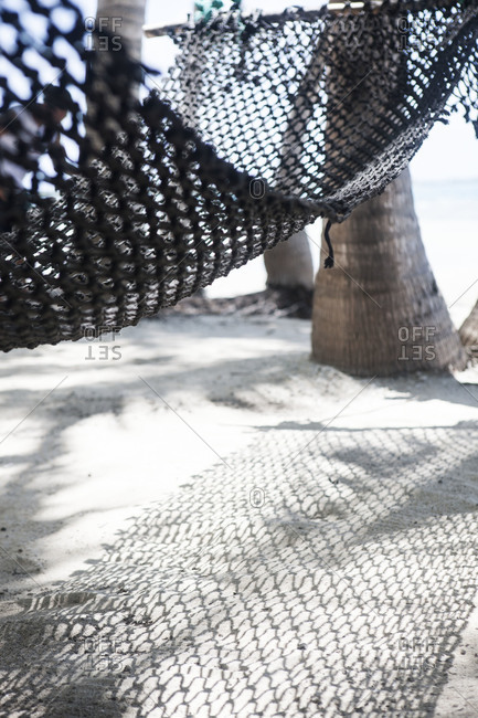 Hammock casting a shadow on white sand