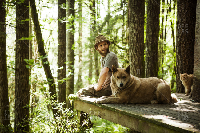 Man sitting in a forest with a dog and with a cat