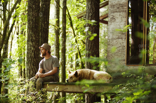 Man sitting at a cabin with a dog