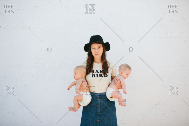 Woman in hat holding twins