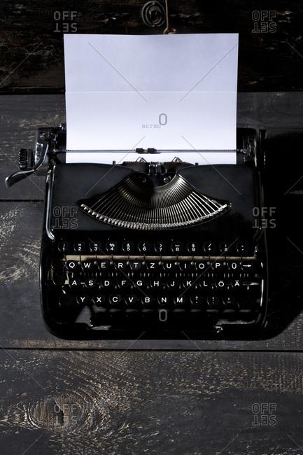 Old black typewriter on dark wood