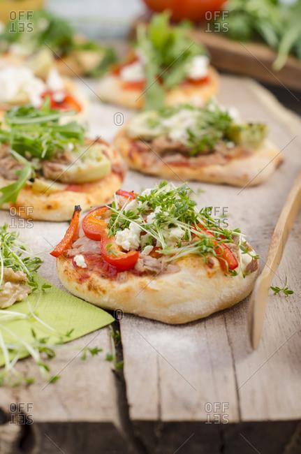 Homemade mini pizzas with arugula, sheep cheese, artichokes, tuna and tomato sauce
