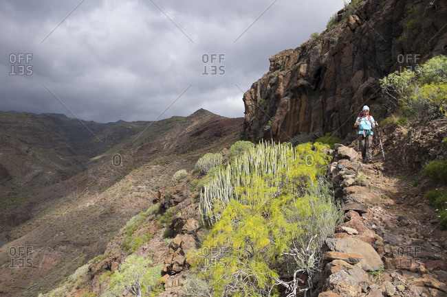 Woman walking on hiking trail Sendero Quise, Canary Islands