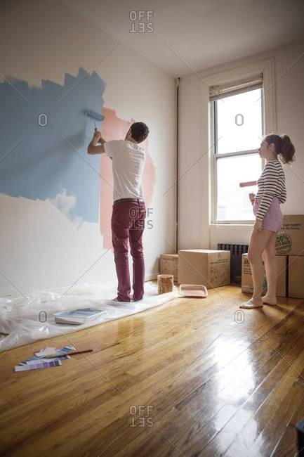 Couple testing out colors of wall paint on their wall