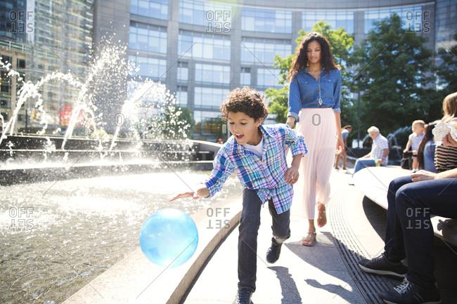 Boy playing with ball around an urban fountain