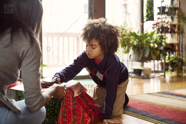 Boy using scissors to open Christmas gifts