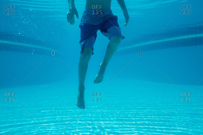 Underwater view of boy's legs swimming in the ocean