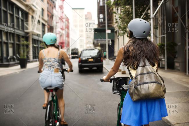 Women riding bike share with helmets