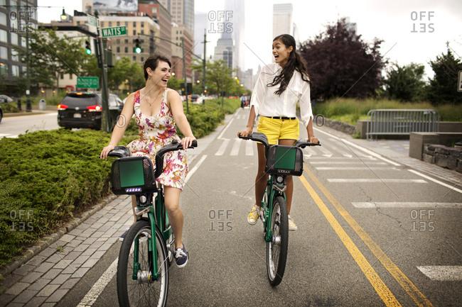 Two woman using bike share in Manhattan, New York City, USA