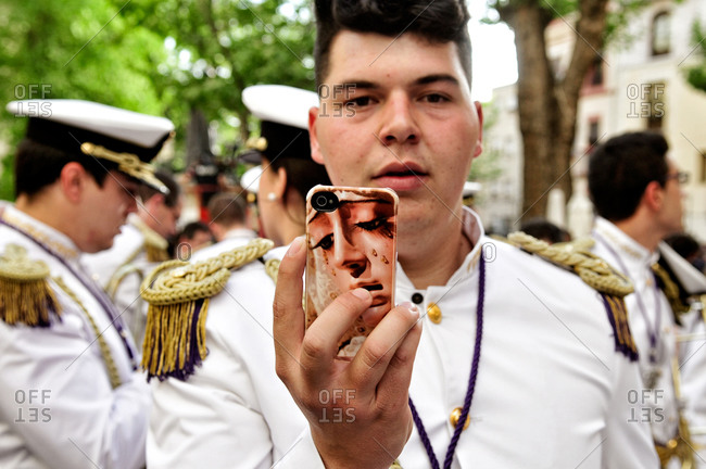 Granada, Spain - April 16, 2014: Member of a marching band showing a Virgin Mary case on his smartphone during Holy Week in Granada, Spain
