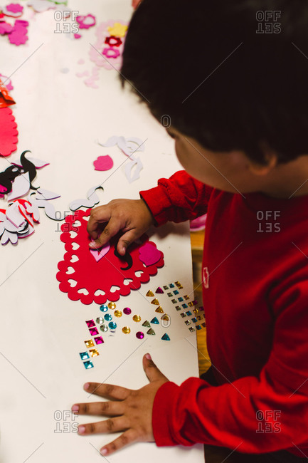 A little boy works on a Valentine\'s Day project