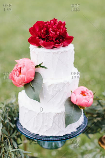 Tiered wedding cake with flowers outside