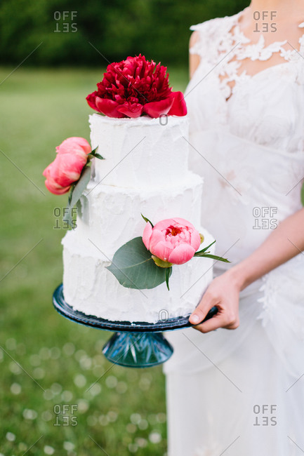 Bride holding wedding cake outside