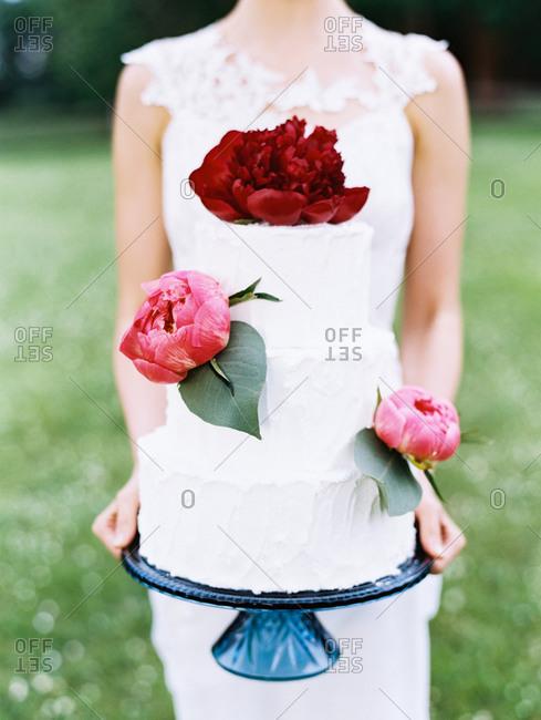 Bride holding up wedding cake