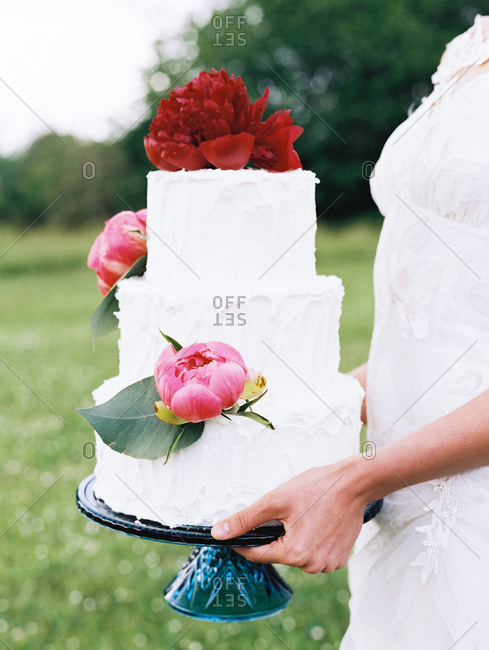 Bride holding floral wedding cake