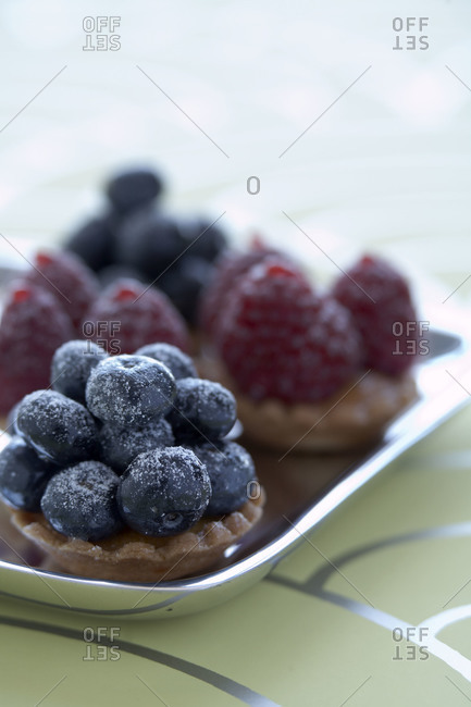 Sugar-coated berry tartlets on a tray
