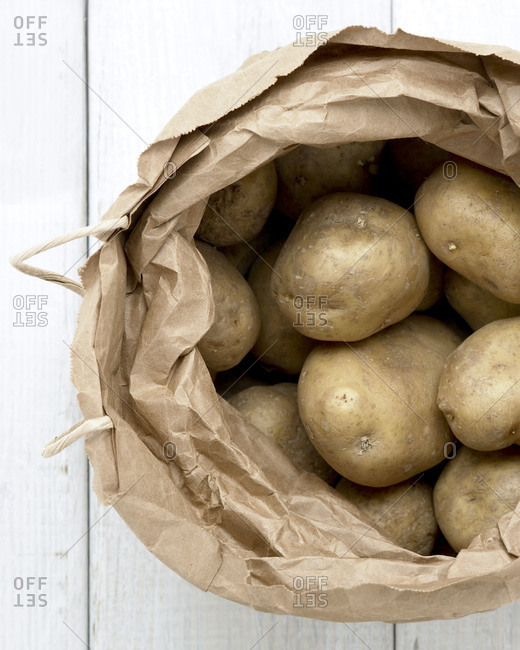 Raw potatoes in a paper bag