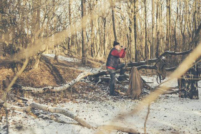Man birdwatching in a winter forest