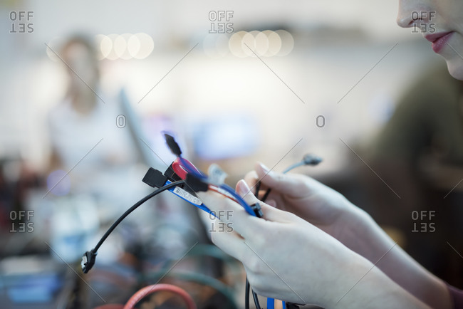 Woman using cables and USB leads in computer repair shop.