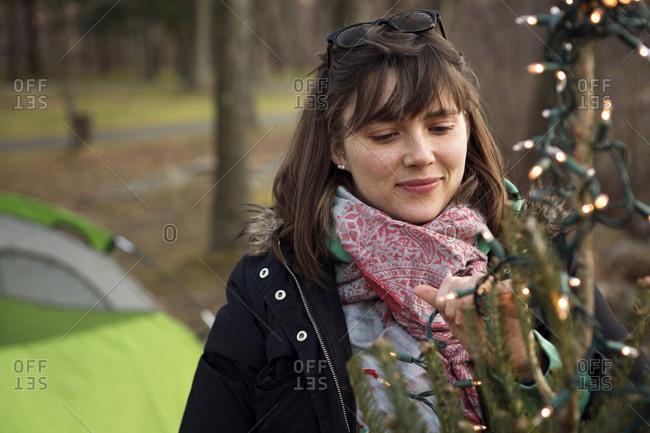 Woman putting lights on an outdoor Christmas tree