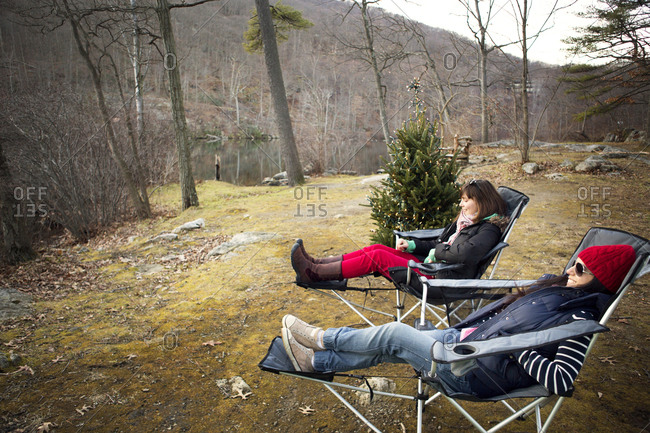 Two women lounging in camp chairs next to a Christmas tree