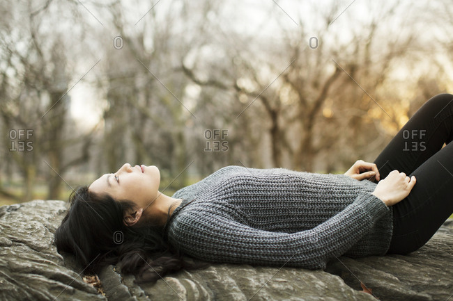 Woman lying on a rock in a park