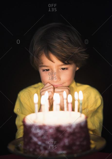 Portrait of boy thinking of birthday wishes, Looking at birthday cake
