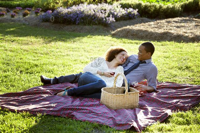 Couple enjoying wine on a picnic blanket