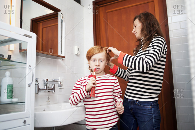 Young boy brushing teeth while his mother fixing his hair