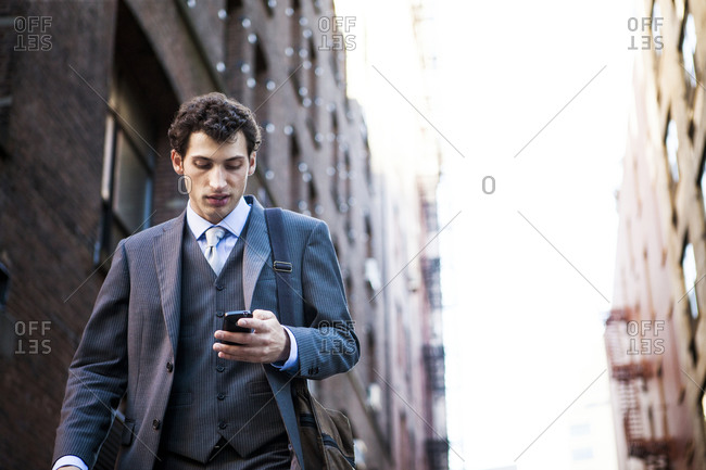 A man walks down the street while checking his cell phone