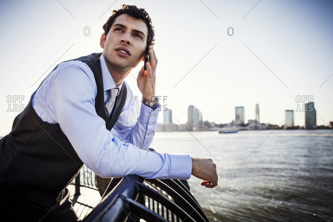 A man makes a call on his cell phone on the waterfront