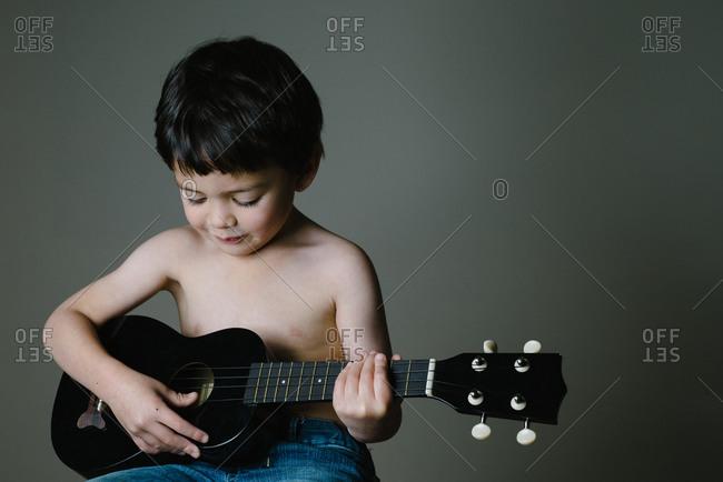 Young boy playing the ukulele