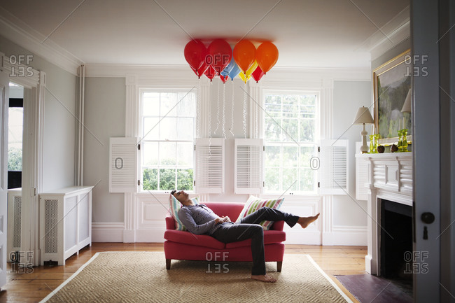 Young man relaxing under a bunch of balloons