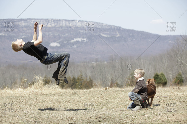 Young boy doing a backflip on a field