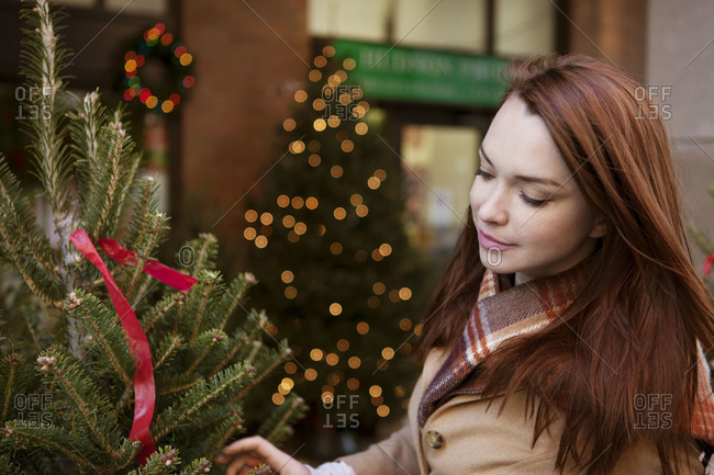 Redhead woman passing by a Christmas tree