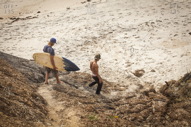Two surfers walking down dunes to bluff