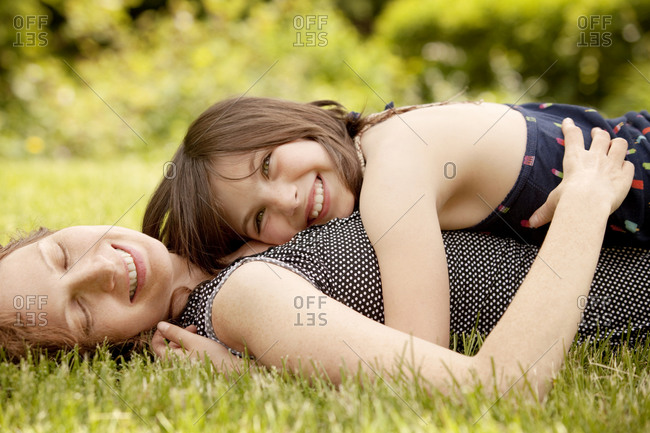 Mother and daughter lying in grass laughing