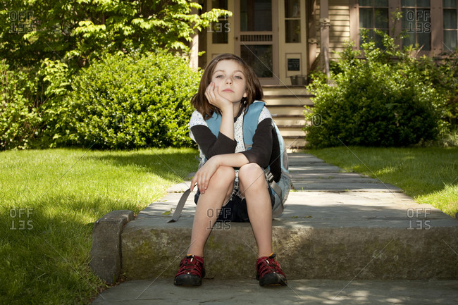 Child waiting for school bus in front of house
