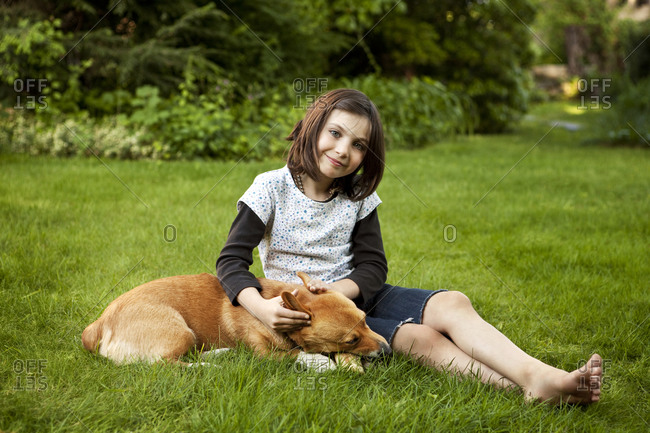 Girl with pet corgi on lawn